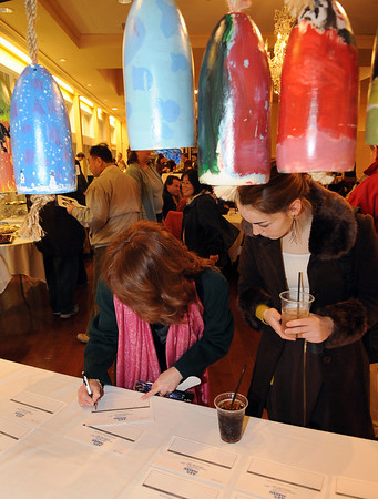 Gloucester: Maryann Delouise and her daughter Corinne 15, places a bid on a buoy she likes, which would support Art Haven's afterschool programs. Desi Smith/Gloucester Daily Times.