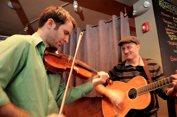 """Jake Armerding, left, plays with  Flynn Cohen during the Sunday brunch at Alchemy Cafe and Bistro.  Cohen is the musical ringleader and brings in a regular rotation of four or five musicians. Cohen said he enjoys playing at Alchemy for the """"amazing food, cool atmosphere, and cool people.""""<br /> Photo by Desi Smith."""