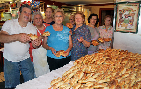 Gail McCarthy/Cape Ann Magazine. Mattoe Favazza, left, owner of Sebastian's Pizzeria in Gloucester, opens his shop at 4 a.m. for the ladies to bake their bread the morning of St. Anthony's birthday. From left are Maria Rubino, Anna Militello, Grace Ciaramitaro, Maria Millefoglie, behind her Fina Maniaci, Margherita Pelliccia, and Caterine Randazza.