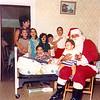 Photo courtesy of the Ciaramitaro family/Cape Ann Magazine. Joseph Ciaramitaro, lying in his bed with Santa Claus, all his sisters and cousins circa 1973.