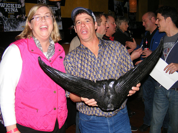 """Gail McCarthy/Cape Ann Magazine. At the """"Wicked Tuna"""" season two premiere in Boston are Gloucester Mayor Carolyn Kirk and deckhand Paul Hebert, known for his colorful personality, who is holding a tuna tail. Hebert ended season one on the Bounty Hunter but is back on the FV-Tuna.com."""