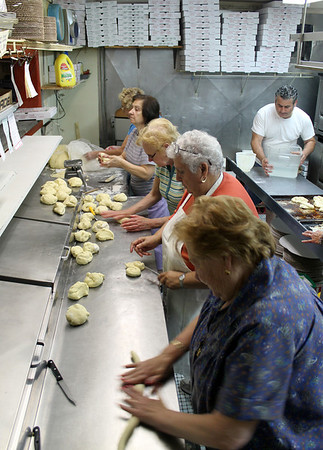 Gail McCarthy/Cape Ann Magazine. Preparing the bread to go into the ovens at Sebastian's Pizzeria early the morning of St. Anthony's birthday are, front to back: Maria Millefoglie, Maria Rubino, Fina Maniaci, Margherita Pelliccia and Grace Ciaramitaro. Sebastian's owner Matteo Favazza is at right lending a hand.