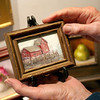 Mary Muckenhoupt/Cape Ann Magazine. Bonnie Crane holds a tiny painting of Motif No. 1 in her Crane Collection/Cape Ann Gallery in Manchester.