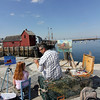 Allegra Boverman/Cape Ann Magazine. Rockport painter Ken Knowles, right, with Sarah Vanderpool of Rockport at T Wharf painting Motif No. 1.