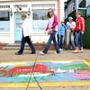 Desi Smith/Cape Ann Magazine. Visitors look at a chalk drawing of the Motif No. 1, drawn by Tom Garrity of Rockport, as they pass through Dock Square during Motif No. 1 Celebration Day.