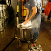 T.J. Peckham removes the lid to prevent the wort from boiling over.<br /> Photo by Kate Glass