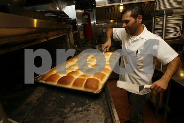 Chef Salvatore Cusenza pulls fresh bread out of the oven at La Trattoria. All their bread is made on site every day. Staff photo by Kate Glass