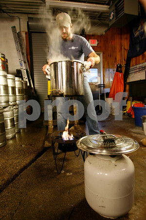 T.J. Peckham removes the boiling wort from the flame to cool.<br /> Photo by Kate Glass