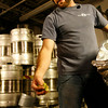 T.J. Peckham adds hops to the wort.<br /> Photo by Kate Glass