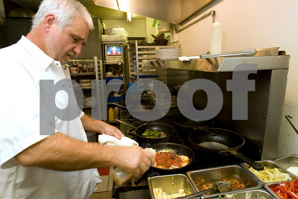 Sal LoGrasso prepares scallops putanesca at his restaurant, LoGrasso's, in Rockport. Staff photo by Kate Glass