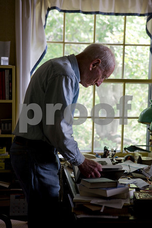 Gloucester author Joe Garland looks through his books in his study.   Photo by Amy Sweeney