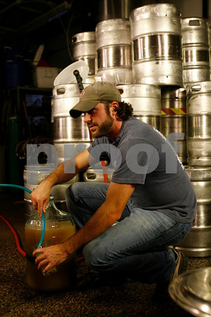 T.J. Peckham of Cape Ann Brewing Company takes a test sample of their small batch strawberry rhubarb beer before the fermentation process.<br /> Photo by Kate Glass