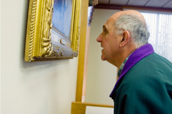 Charles Movalli, who has written three books on painter Emile Gruppe, looks at one of Gruppe's paintings that is hanging in the Cape Ann Savings Bank. Photo by Amy Sweeney.