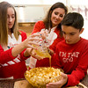 Felicia Mohan and her children, Amanda and B.J., pour a mixture of honey and corn syrup over the Pinulatas.