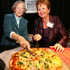 Gloucester: Elizabeth Neumeier and Bea Waring, President of the Gloucester Stage Company Board of Directors, slice pizza for their end of season party. Photo by Kate Glass/Cape Ann Magazine