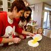 Eleanor Curcuru and Felicia Mohan pour beaten eggs into a pile of durham wheat flour to form the dough for Pinulata as their nieces, Eloise Ciaramitaro, 5, and Madeline Ciaramitaro, 3, watch.