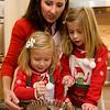 Felicia Mohan watches as her nieces, Madeline Ciaramitaro, 3, and Eloise Ciaramitaro, 5, stir honey and corn syrup for the Pinulatas.