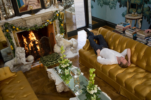 """Alexander Westerhoff relaxes in the living room of """"Serenity"""" the home he and Tom Lang own in Manchester-by-the-Sea. <br /> The mantel is from the Doris Duke estate in Newport, R.I. mid 18th-Century English, which they painstakling restored.<br /> The marble Venetian  lions flanking the fireplace are early 17th-Century."""
