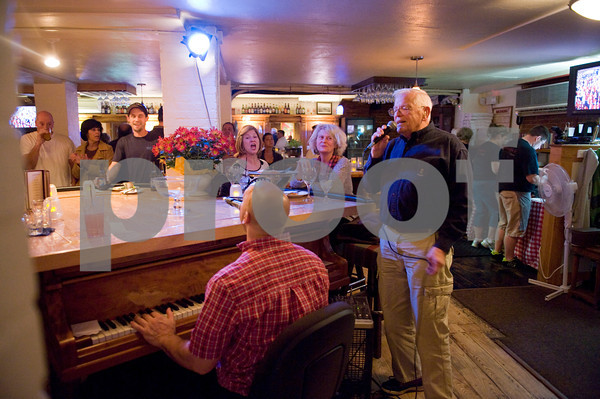 """William Shepard -- """"Wild Bill""""  as Joe calls regular  has been singing with Joe since the 90's at the Studio on Rocky Neck <br />  He belts out a tune during a Saturday night piano bar session at Giuseppe's Ristorante and Piano Bar with owner Joe at the piano.<br /> Photo by Desi Smith."""