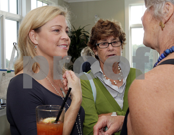 Heather Outlaw, left, and Lee Bresnahan, center, admire some jewelry at the seARTS Fashion Show at Bass Rocks Country Club. David Le/Cape Ann Magazine