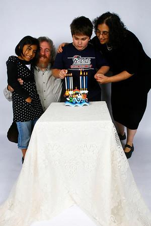 Gloucester: Rabbi Samuel Barth, his wife, Karen, and children, Miriam, 9, and Yishai, 12, light a menorah for Hanukkah. Photo by Kate Glass