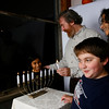 Gloucester: Rabbi Samuel Barth, his wife, Karen, and children, Miriam, 9, and Yishai, 12, light a menorah for Hanukkah. Photo by Kate Glass