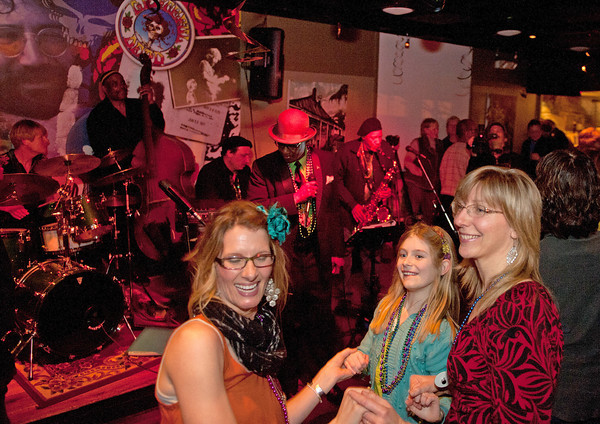Gloucester:  Patry goer's Syliva Lessa, Cara Buchanan 9, and Shay Cajolet dance at a Mardi Gras fundraiser party at Minglewood Tavern/Latitude 43. Henri Smith's New Orleans style band and Grammy winner saxophonist Charles Neville played the music. Desi Smith/ Gloucester Daily Times. February 21,2012.