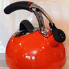 Oxo Uplift Kettle in orange, it whistles and comes with a cushioned<br /> heat resistant handle. Lulu's Pantry.