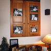 "An armoire no longer in use was repurposed. The large wooden cabinet doors are now mounted on the wall and display several 8x10 family portraits in a unique frame job, above which is a sign that states: ""All because two people fell in love.""<br /> Photo by Allegra Boverman"