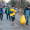 Desi Smith/Staff Photo.  From left to right, Lois McNulty, Kathryn Goodick, Donna Ardizzoni and Amy Kerr, make their way on Dogtown Road off Cherry Street to clean up a teen party spot in the woods. The One Hour at a Time Gang, Led by Donna Ardizzoni and Clean Gloucester, led by Amy Kerr, meet for one hour every Saturday with help from a dedicated team of volunteers at 8 to clean up trash in one area in the city.    November 30,2014