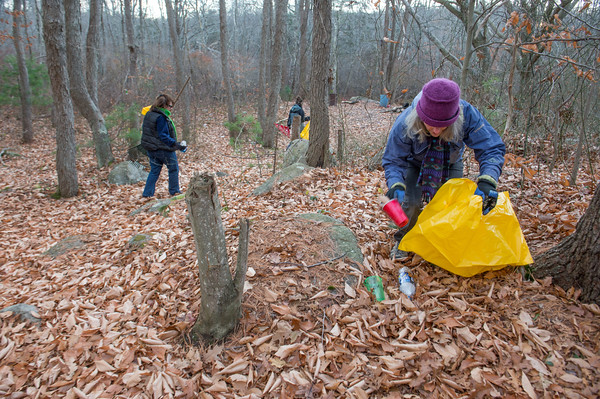 Desi Smith/Staff photo. Lois McNulty, right, starts in on picking up trash left by teens at a party spot in the woods off Cherry Street in Gloucester, as volunteers Kathryn Goodick, Donna Ardizzoni and Amy Kerr seek trash further in the woods. The One Hour at a Time Gang, led by Ardizzoni, and Kerr of Clean Gloucester organized the cleanup as part of their regular Saturday morning fight against litter in the city.