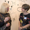 Desi Smith/Cape Ann Magazine.  Artist Margaret Rack, right talks with Yvonne Lindsay of Middleborough about her work that hangs behind them at the opening exhibit of retrospective celebrating 30 years of Cape Ann Artisans held on March 2 at Cape Ann Museum. Tracey is wearing one of Beth's pieces around her neck.
