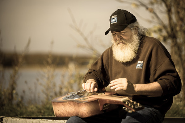 "Desi Smith/Cape Ann Magazine. Paul ""Sasquatch"" Cohan plays a resonator, or Dobro, guitar in the steel guitar style — strings are plucked with one hand, while the other hand changes the pitch of one or more strings, often with the use of a bar or slide called a steel."