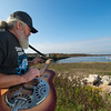 "Desi Smith/Cape Ann Magazine. Paul ""Sasquatch"" Cohan plays one of his guitar along the Annisquam River, behind his Sasquatch Smokehouse, near the end of Whittemore Street in Gloucester."