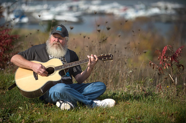 "Desi Smith/Cape Ann Magazine. Paul ""Sasquatch"" Cohan plays one of his guitars along the Annisquam River, behind his Sasquatch Smokehouse, near the end of Whittemore Street in Gloucester."
