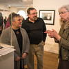 Desi Smith/Cape Ann Magazine. Richard and Tracey Nestel of Rockport talk to jewelry maker Beth Williams, at the opening exhibit of retrospective celebrating 30 years of Cape Ann Artisans held on March 2 at Cape Ann Museum. Tracey is wearing one of Beth's pieces around her neck.