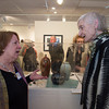 Desi Smith/Cape Ann Magazine. Artist Marty Morgan talks with Patricia Sutherland at the opening exhibit of retrospective celebrating 30 years of Cape Ann Artisans held on March 2 at Cape Ann Museum. Displayed in the case are her works.