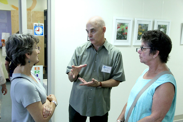 "Vincenzo Dimino photo<br /> Dr. Brian Orr, center, talks about his stained glass art with Denice Kolsch, left, and Emily Krishna of Beverly. Orr hosted ""Windows on the World; "" a public art reception and open house at his pediatric offices at the Cape Ann Medical Center in Gloucester to benefit Nuestros Pequeños Hermanos, which supports nine orphanages in Central and South America. """