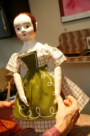 Allegra Boverman/Cape Ann Magazine. Peggy Flavin of Annisquam recreates dolls from the past. She is putting a new pinafore on Lucy.