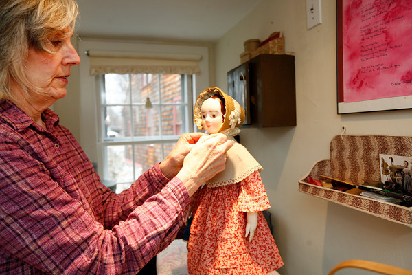 Allegra Boverman/Cape Ann Magazine. Peggy Flavin of Annisquam recreates dolls from the past. She is dressing Lucy.