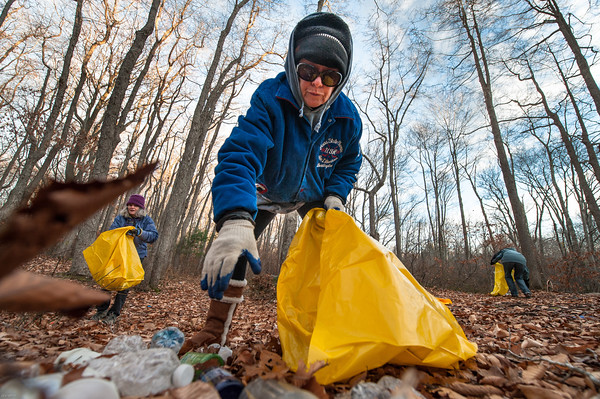 Desi Smith/Staff Photo.  Donna Ardizzoni starts in on a pile of trash left by partiers in the woods off Cherry Street, with some help from volunteers Lois McNulty,(left) and Kathryn Goodick. The One Hour at a Time Gang, Led by Donna Ardizzoni and Clean Gloucester, led by Amy Kerr, who meet for one hour every Saturday with help from a dedicated team of volunteers at 8 to clean up trash in one area in the city.    November 30,2014