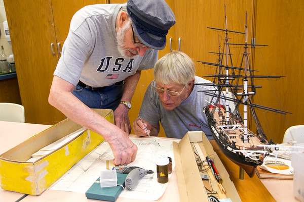 Photo/Reba Saldanha Marci Consalvo, left, and Curt Hill work together during a model ship building class at Peabody's senior center Sept 12, 2016.