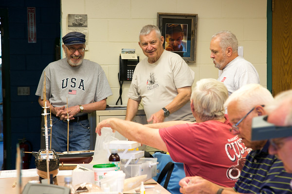 Photo/Reba Saldanha Marci Consalvo, left, and Lloyd Sanborn, chat with Ed Croughwell, seated, during a model ship building class at Peabody's senior center Sept 12, 2016.