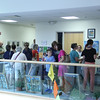 """Vincenzo Dimino photo<br /> A crowd fills the lobby at the Cape Ann Medical Center in Gloucester where Dr. Brian Orr hosted """"Windows on the World,"""" a public art reception and open house at his pediatric offices to benefit Nuestros Pequeños Hermanos, which supports nine orphanages in Central and South America."""