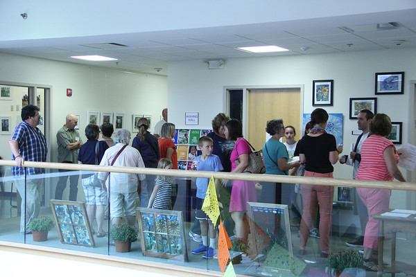 "Vincenzo Dimino photo<br /> A crowd fills the lobby at the Cape Ann Medical Center in Gloucester where Dr. Brian Orr hosted ""Windows on the World,"" a public art reception and open house at his pediatric offices to benefit Nuestros Pequeños Hermanos, which supports nine orphanages in Central and South America."