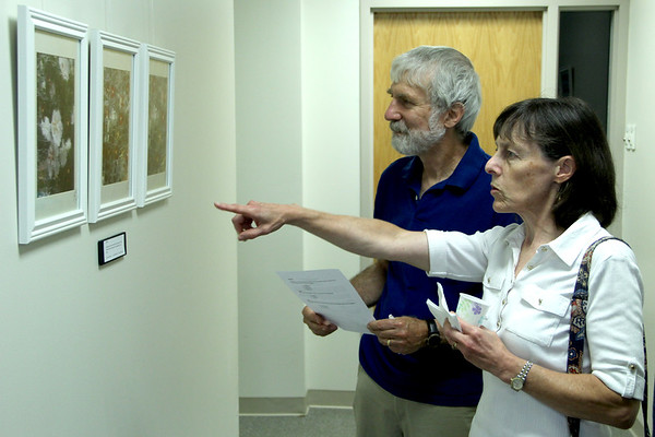 "Vincenzo Dimino photo​<br /> Nancy Schalch and Robert Buchsbaum, both of Beverly, look at photographs from the ""Quisqueya Dreams: Images of Dominican Republic""f by Kara Swenson of Topsfield. wenson and artist Dr. Brian Orr hosted ""Windows on the World,"" a public art reception and open house at Orr's pediatric offices at the Cape Ann Medical Center in Gloucester to benefit Nuestros Pequeños Hermanos, which supports nine orphanages in Central and South America."