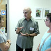 """Vincenzo Dimino photo<br /> Dr. Brian Orr, center, talks about his stained glass art with Denice Kolsch, left, and Emily Krishna of Beverly. Orr hosted """"Windows on the World; """" a public art reception and open house at his pediatric offices at the Cape Ann Medical Center in Gloucester to benefit Nuestros Pequeños Hermanos, which supports nine orphanages in Central and South America. """""""