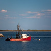 red fishing boat at end of Provincetown Harbor breakwater