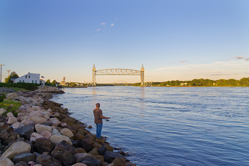 angler watching sun set on Cape Cod Railroad Bridge