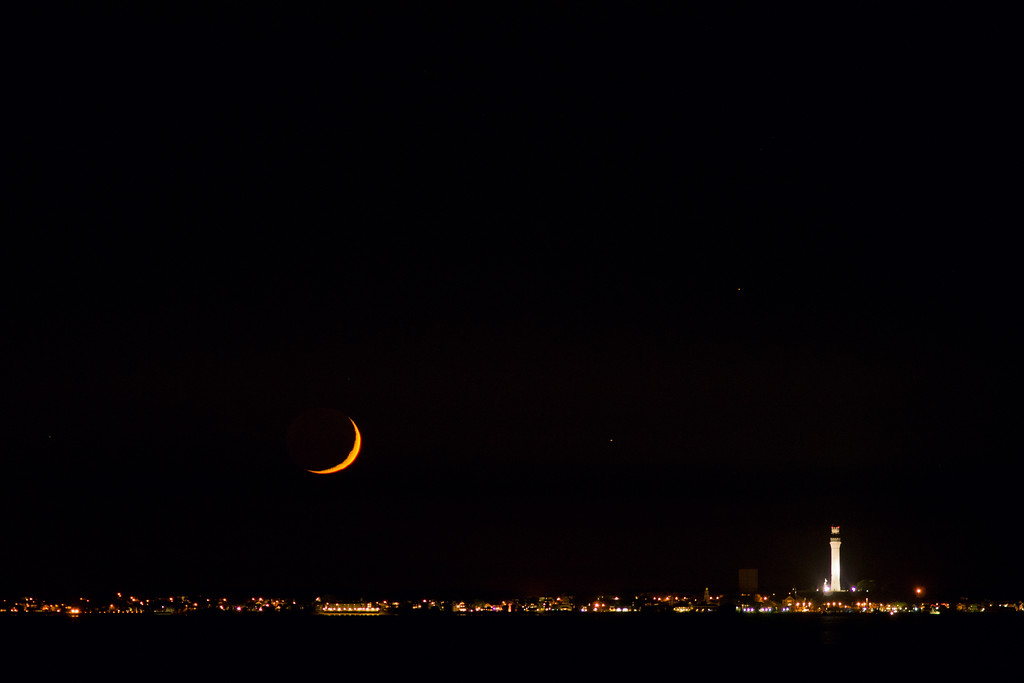 red crescent moon setting over Provincetown